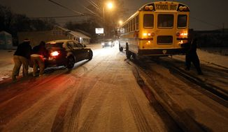 People work to push a stuck Atlanta school bus and a car on an icy stretch of University Avenue in Southwest Atlanta on Tuesday, Jan. 28, 2014. The bus was eventually moved off the road and left for the night. (AP Photo/Atlanta Journal-Constitution, Ben Gray) MARIETTA DAILY OUT; GWINNETT DAILY POST OUT; LOCAL TV OUT; WXIA-TV OUT; WGCL-TV OUT.