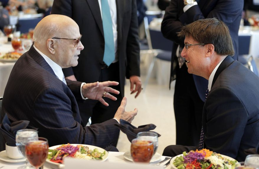 Charlotte Motor Speedway chairman Bruton Smith, left, talks with North Carolina Gov. Pat McCrory, right, before a news conference at the NASCAR Sprint Cup auto racing Media Tour in Charlotte, N.C., Monday, Jan. 27, 2014. (AP Photo/Chuck Burton)