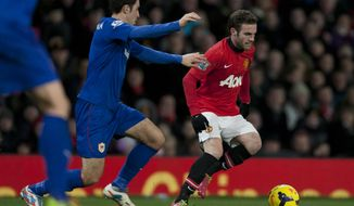 Manchester United's Juan Mata, right, keeps the ball from Cardiff City's Peter Whittingham during their English Premier League soccer match at Old Trafford Stadium, Manchester, England, Tuesday Jan. 28, 2014. (AP Photo/Jon Super)