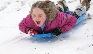Lily Turcotte-Keen, 8, screams as she sleds down a hill at Grant Park after getting out of school early due to the snow storm on Tuesday, Jan. 28, 2014, in Atlanta. A winter storm that would probably be no big deal in the North all but paralyzed the Deep South on Tuesday, bringing snow, ice and teeth-chattering cold, with temperatures in the teens in some places. (AP Photo/Atlanta Journal-Constitution, Ben Gray)