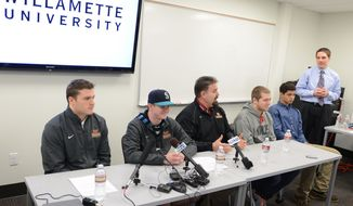 Conner Mertens, second from left, a redshirt freshman place kicker at Willamette University, attends a news conference at the university in Salem, Ore., on Tuesday, Jan. 28, 2014. Defensive captain Jack Nelson, left, coach Glen Fowles, center, and others joined Mertens. Merters announced that he is bisexual, saying he was tired of pretending he was something he wasn't. (AP Photo/Statesman Journal, Danielle Peterson)