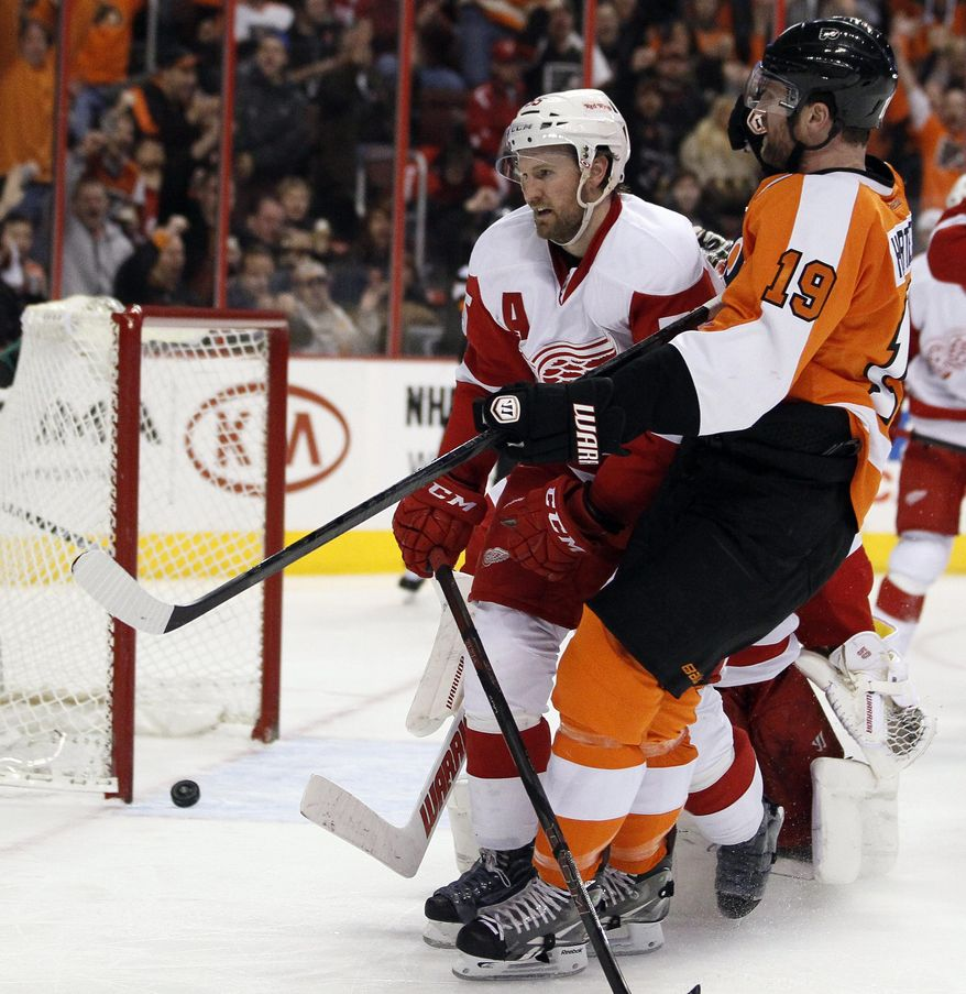 The gola scored by Philadelphia Flyers' Scott Hartnell, right, rolls back out of the net as Detroit Red Wings' Niklas Kronwall, left, skates past during the second period of an NHL hockey game, Tuesday, Jan. 28, 2014, in Philadelphia. (AP Photo/Tom Mihalek)