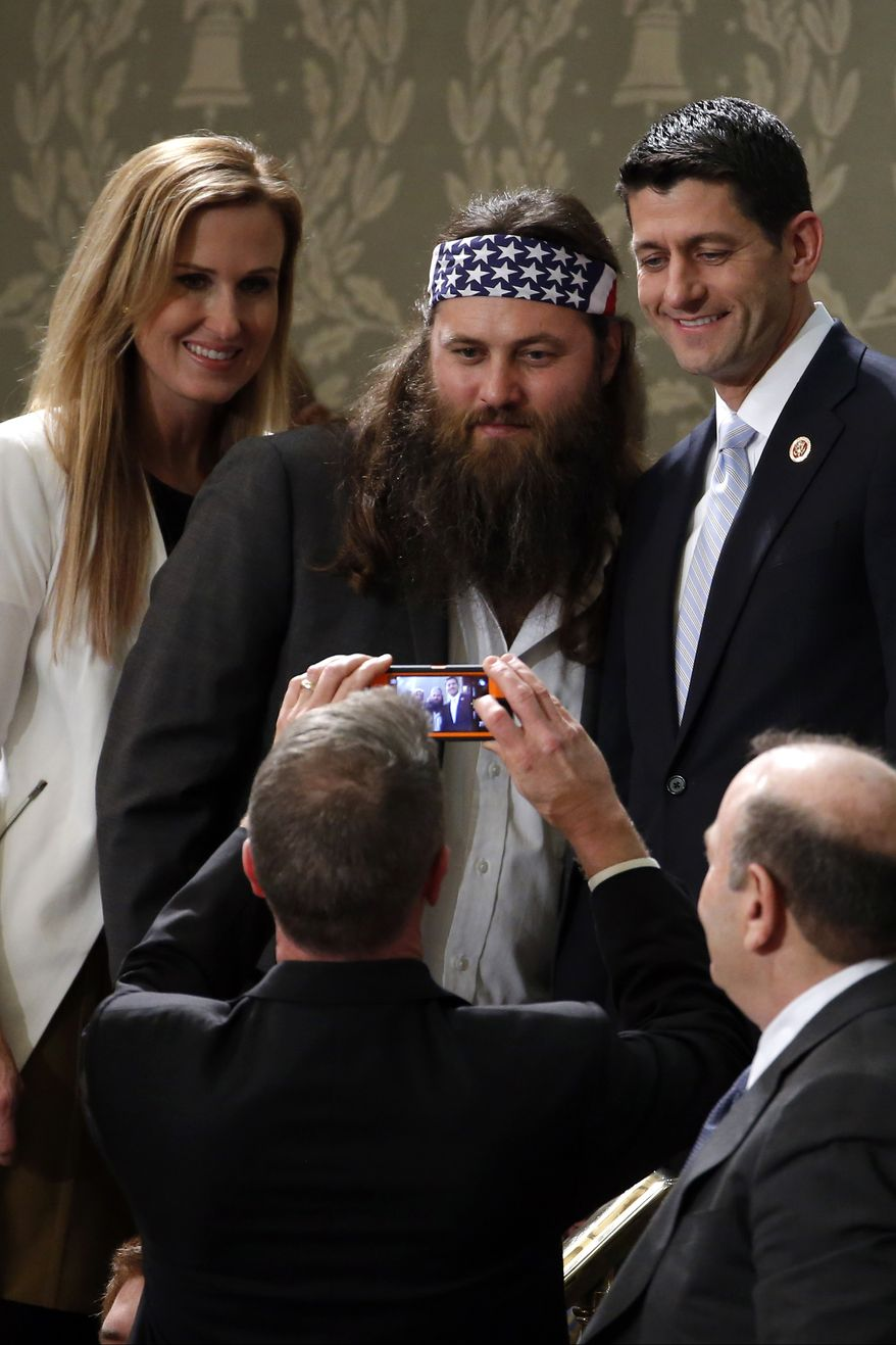 Duck Dynasty's Willie Robertson, center and his wife Korie, pose with Rep. Paul Ryan, R-Wis., before President Barack Obama's State of the Union address on Capitol Hill in Washington, Tuesday Jan. 28, 2014. (AP Photo/Charles Dharapak)