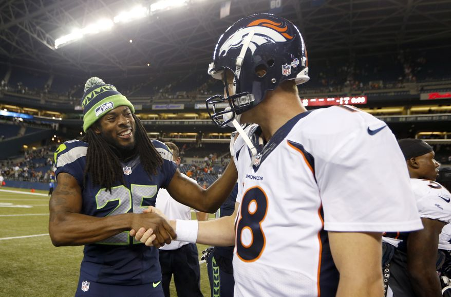 In this photo taken Aug. 17, 2013, Seattle Seahawks cornerback Richard Sherman, (25) shakes hands with Denver Broncos quarterback Peyton Manning, right, after the Seahawks beat the Broncos 40-10, in a preseason NFL football game in Seattle. The two teams square off in Super Bowl XLVIII on Sunday, Feb. 2, 2014, in East Rutherford, N.J.  (AP Photo/John Froschauer)