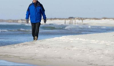 """Tim Carr takes a walk along the beach on Okaloosa Island in Fort Walton Beach, Fla., on Wednesday, Jan.  22, 2014, where the temperature was hovering in the low 30s. """"I don't like it when it's so cold,"""" said Carr, """"but I've got a bunch of layers on."""" (AP Photo/Northwest Florida Daily News, Devon Ravine)"""