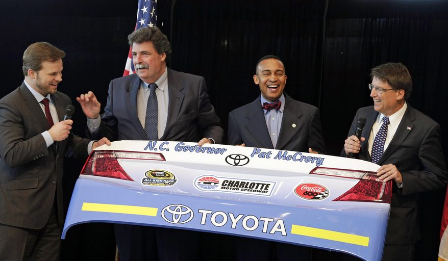 North Carolina Gov. Pat McCrory, right, holds a race car bumper with Charlotte, N.C., mayor Patrick Cannon, second from right, and NASCAR president Mike Helton, second from left, after McCrory was presented with it by Charlotte Motor Speedway president Marcus Smith, left, during a news conference at the NASCAR Sprint Cup auto racing Media Tour in Charlotte, N.C., Monday, Jan. 27, 2014. (AP Photo/Chuck Burton)
