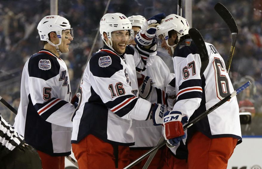 New York Rangers left wing Benoit Pouliot (67) celebrates wtith teammates after scoring a goal in the second period of an outdoor NHL hockey game against the New York Islanders at Yankee Stadium in New York, Wednesday, Jan. 29, 2014.  (AP Photo/Kathy Willens)