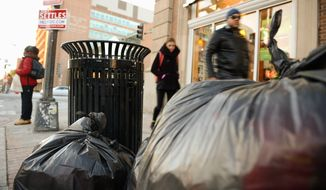 Trash piles up on the corner of U and 14th streets in Northwest as D.C. crews struggled to provide services hit by last week's snowstorm that made streets inaccessible. (andrew harnik/the Washington Times)