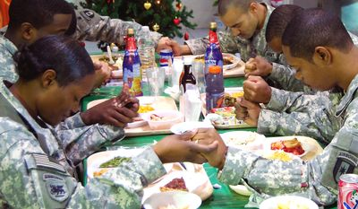 A group of USACE Soldiers take time to say a prayer of thanksgiving before starting their meal.Ê They all come from different cities, backgrounds and beliefs, but they are united by love of their country, the Army and the belief that theyÕre doing good work in helping the IraqisÕ rebuild their nation.Ê (Photo by Van Williams, USACE)