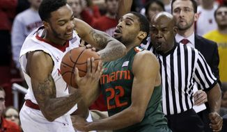 Maryland guard Roddy Peters, left, wrestles the ball away from Miami forward Donnavan Kirk in the first half of an NCAA college basketball game in College Park, Md., Wednesday, Jan. 29, 2014. (AP Photo/Patrick Semansky)