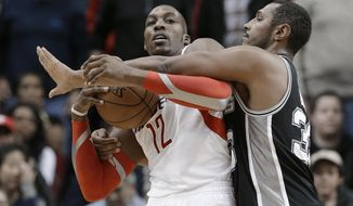 Houston Rockets' Dwight Howard (12) is fouled by San Antonio Spurs' Boris Diaw (33) during the second half of an NBA basketball game Tuesday, Jan. 28, 2014, in Houston. The Rockets won 97-90. (AP Photo/Pat Sullivan)