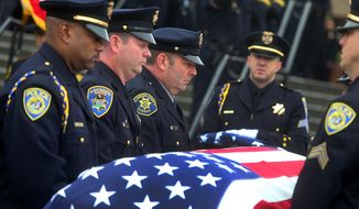 Pallbearers carry the casket of Bay Area Rapid Transit police Sgt. Tom Smith Jr. into the chapel during funeral services at the Neighborhood Church on Wednesday, Jan 29, 2014, in Castro Valley, Calif. Smith Jr.'s brother-in-law Hayward Police Officer Todd Shaheen is second to left, and brother Alameda County Sheriff Deputy Ed Smith is third from left. Smith, 42, died last week after being shot by fellow BART officer Michael Maes during an apartment search at an apartment complex in Dublin, Calif. (AP Photo/Bay Area News Group, Aric Crabb) MANDATORY CREDIT.