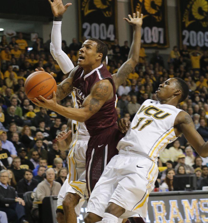 Fordham's Chris Whitehead draws a foul from VCU's Rob Brandenberg (11) during an NCAA college basketball game Wednesday, Jan. 29, 2014, in Richmond, Va. (AP Photo/Richmond Times-Dispatch, Joe Mahoney)