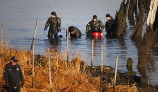 FILE - In this Friday, Jan. 17, 2014, file photo, after an arm, torso and legs were discovered a day earlier, a New York Police Department dive unit continues the search for human remains along a rocky shoreline in the Queens borough of New York. The remains were those of missing autistic teenager Avonte Oquendo. The U.S. Department of Justice said Wednesday, Jan. 29, 2014, it will fund voluntary tracking devices for children with autism or other conditions that put them at risk for fleeing their caregivers. (AP Photo/Jason DeCrow, File)