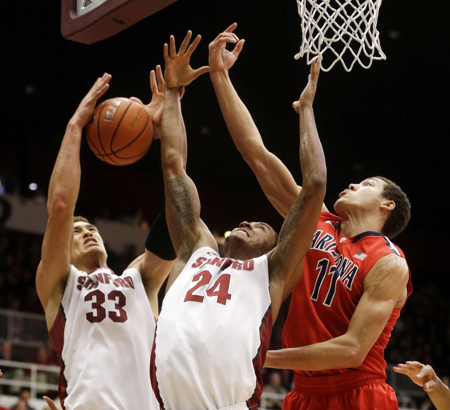 Stanford forward Dwight Powell (33) grabs a rebound next to teammate Josh Huestis (24) and Arizona forward Aaron Gordon (11) during the first half of an NCAA college basketball game on Wednesday, Jan. 29, 2014, in Stanford, Calif. (AP Photo/Marcio Jose Sanchez)