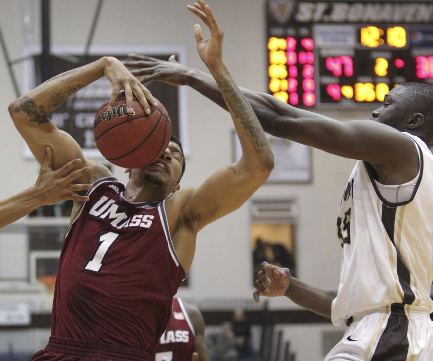 Massachusetts forward Maxie Esho (1) takes the ball to his face after St. Bonaventure center Youssou Ndoye (35) blocked his shot during the second half of an NCAA college basketball game in St. Bonaventure, N.Y., Wednesday, Jan 29, 2014. St. Bonaventure won 78-65. (AP Photo/Nick LoVerde)