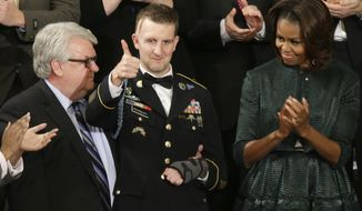 Craig Remsburg, father of Army Ranger Sgt. 1st Class Cory Remsburg, center, watches as his son acknowledges applause from first lady Michelle Obama and others during President Barack Obama's State of the Union address on Capitol Hill in Washington, Tuesday Jan. 28, 2014. (AP Photo/J. Scott Applewhite)