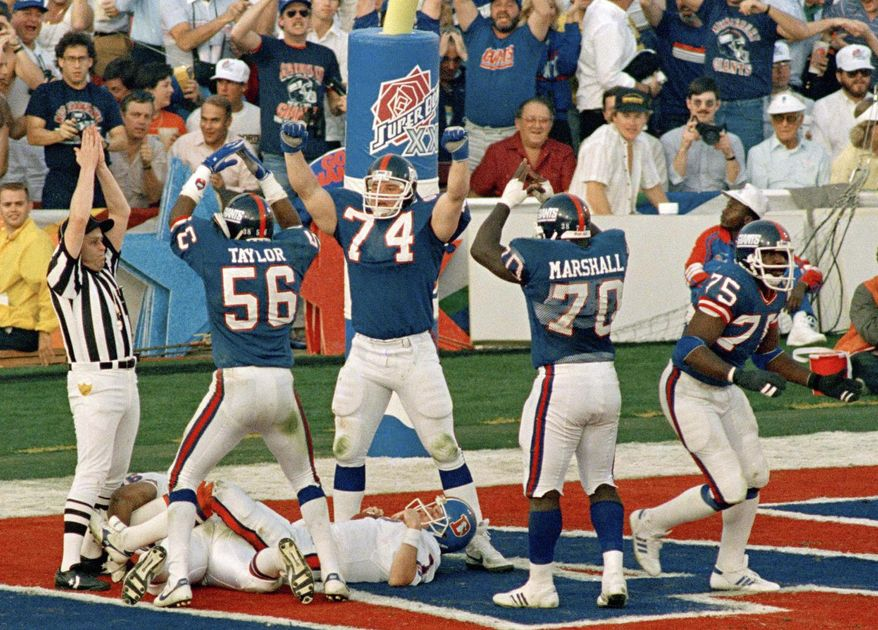 FILE - In this Jan. 25, 1987, file phot, New York Giants defense Lawrence Taylor (56), Erik Howard (74) and Leonard Marshall (70) celebrate over Denver broncos quarterback John Elway after he was sacked by George Martin (75) for safety in the second quarter of Super Bowl XXI in Pasadena, Calif. (AP Photo/Ron Heflin, File)
