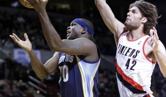 Memphis Grizzlies forward Zach Randolph, left, drives to the basket past Portland Trail Blazers center Robin Lopez during the first half of an NBA basketball game in Portland, Ore., Tuesday, Jan. 28, 2014. (AP Photo/Don Ryan)