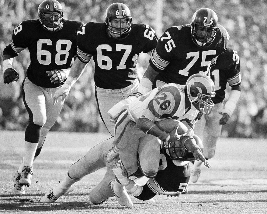 FILE - In this Jan. 20, 1980, file photo, Los Angeles Rams running back Wendell Tyler (26) is thrown for 4-yard loss by Pittsburgh Steelers linebacker Jack Lambert (58) as Steelers; L.C. Greenwood (68), Gary Dunn (67) and Joe Greene (75) during first quarter of Super Bowl XIV at the Rose Bowl in Pasadena, Calif.  (AP Photo/File)
