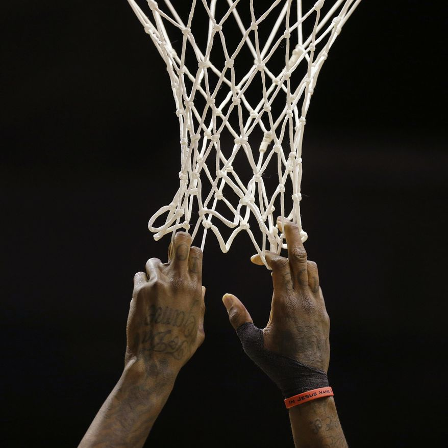 Milwaukee Bucks' Larry Sanders grabs the net during a break in the action in the first half of an NBA basketball game against the Phoenix Suns on Wednesday, Jan. 29, 2014, in Milwaukee. (AP Photo/Jeffrey Phelps)