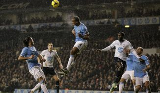 Manchester City's Vincent Kompany, center, clears the ball away during the English Premier League soccer match between Tottenham Hotspur and Manchester City at White Hart Lane stadium in London, Wednesday, Jan. 29, 2014.  (AP Photo/Matt Dunham)