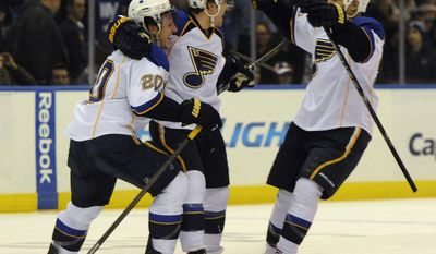 St. Louis Blues' Alexander Steen (20), Kevin Shattenkirk, center and Chris Stewart, right, celebrate their 4-3 shootout win over the New York Islanders in an NHL hockey game on Saturday, Jan. 25, 2014, in Uniondale, N.Y. Shattenkirk scored the winning goal against Islanders goalie Kevin Poulin. (AP Photo/Kathy Kmonicek)