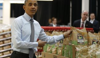 President Barack Obama holds up a bag of tortilla chips during a visit at a Costco store in Lanham, Md., Wednesday, Jan. 29, 2014, where he spoke about raising the minimum wage the morning after his State of the Union address.  (AP Photo/Charles Dharapak)