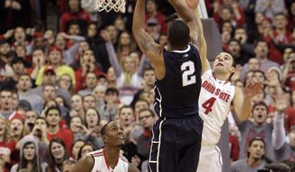 Penn State's DJ Newbill (2) makes the game-winning shot as Ohio State's Aaron Craft, right, and Sam Thompson, left, defend during overtime of an NCAA college basketball game Wednesday, Jan. 29, 2014, in Columbus, Ohio. Penn State beat Ohio State 71-70 in overtime. (AP Photo/Jay LaPrete)