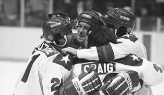 Michael Eruzione, left, scorer of the decisive fourth goal for the USA in the game against USSR on Feb. 22, 1980 in Lake Placid, is embraced by team mates John O'Callahan, David Silk, and goalie James Craig after he brought his team into the lead. (AP Photo)