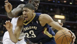 New Orleans Pelicans' Anthony Davis (23) drives past Cleveland Cavaliers' Anthony Bennett (15) during the fourth quarter of an NBA basketball game, Tuesday, Jan. 28, 2014, in Cleveland. New Orleans defeated Cleveland 100-89. (AP Photo/Tony Dejak)