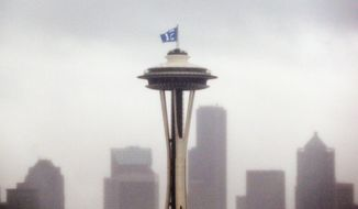 "A ""12th Man"" flag, honoring Seattle Seahawks fans, is barely visible as it flutters atop the Space Needle in the rain Wednesday, Jan. 29, 2014, in Seattle. The Seahawks play the Denver Broncos in Super Bowl XLVIII on Sunday. (AP Photo/Elaine Thompson)"