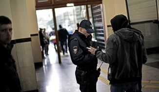A police officer checks the identification of a passerby in the central train station, Wednesday, Jan. 29, 2014, in Sochi, Russia, home of the upcoming 2014 Winter Olympics. (AP Photo/David Goldman)