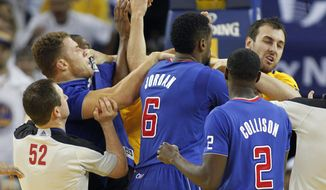 FILE - In this Dec. 25, 2013, file photo, Los Angeles Clippers power forward Blake Griffin, left, fights with Golden State Warriors center Andrew Bogut, right, as Clippers center DeAndre Jordan (6) and Darren Collison (2) look on during the second half of an NBA basketball game in Oakland, Calif. Griffin was ejected from the game. Whether the Warriors and Clippers are growing into unlikely California rivals might still be up for debate. This much is clear: neither team likes the other. The Pacific Division-leading Clippers visit the Warriors on Thursday night for the first time since Golden State's win on Christmas was marred by multiple technical fouls, elbows and heated verbal exchanges. (AP Photo/Tony Avelar, File)