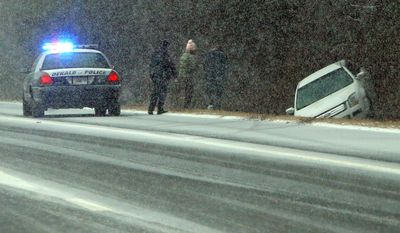 A Dekalb Police officer stops to check on Jesse Hatcher after he says another motorist caused him to lose control of his car and spin into the ditch off I-20 West near Conyers on Tuesday, Jan. 28, 2014, in Conyers.  (AP Photo/Atlanta Journal-Constitution, Curtis Compton)