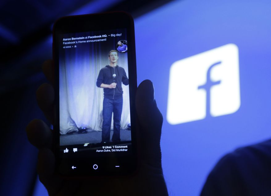 FILE- In this Thursday, April 4, 2013, photo, Michael Goodwin, Senior Partner for HTC, displays an HTC First cell phone wit the new Facebook interface at Facebook headquarters in Menlo Park, Calif. Facebook reports quarterly financial results on Wednesday, Jan. 29, 2014. (AP Photo/Marcio Jose Sanchez, File)