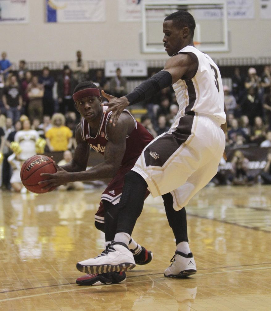 Massachusetts guard Chaz Williams, left, looks to pass around St. Bonaventure guard Charlon Kloof during the first half of an NCAA college basketball game in St. Bonaventure, N.Y., Wednesday, Jan. 29, 2014. (AP Photo/Nick LoVerde)