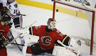 Chicago Blackhawks' Jonathan Toews, left, watches the puck pass over the head of Calgary Flames goalie Reto Berra, from Switzerland, during second period NHL hockey action in Calgary, Canada, Tuesday, Jan. 28, 2014. (AP Photo/The Canadian Press, Jeff McIntosh)