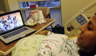 In this image taken on Monday, Jan. 27, 2014, and released by Bethune-Cookman, Vanessa Blair-Lewis, Bethune-Cookman women's basketball coach, watches an internet broadcast of her team's game after giving birth to son Blair Eric Lewis at Halifax Health Medical Center in Port Orange, Fla. (AP Photo/Bethune-Cookman