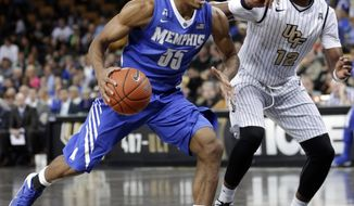 Memphis' Geron Johnson (55) drives to the basket past Central Florida's Matt Williams (12) during the first half of an NCAA basketball game in Orlando, Fla., Wednesday, Jan. 29, 2014.(AP Photo/John Raoux)