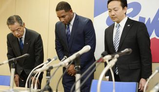 Yakult Swallows slugger Wladimir Balentien, center, bows during a press conference in Tokyo Wednesday, Jan. 29, 2014. Balentien has apologized to his fans, several days after pleading not guilty to domestic violence charges in Florida. As is the custom in Japan, Balentien bowed deeply and then apologized Wednesday to his fans and teammates for the actions that led to his arrest on Jan. 13. (AP Photo/Kyodo News) JAPAN OUT, MANDATORY CREDIT