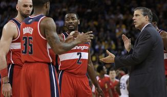 Washington Wizards coach Randy Wittman, right, speaks with Trevor Booker (35), Marcin Gortat, left, and John Wall (2) during the first half of an NBA basketball game against the Golden State Warriors, Tuesday, Jan. 28, 2014, in Oakland, Calif. (AP Photo/Ben Margot)