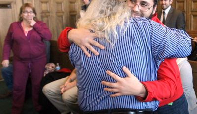 Dewey Jones embraces his son, Zack, in a gallery of family and friends after a hearing before Summit County Common Pleas Court Judge Mary Margaret Rowlands on Thursday, Jan. 30, 2014 in Akron, Ohio.   Prosecutors have dismissed charges against jones who served about 20 years in prison for a 1993 killing  though he maintained his innocence.  (AP Photo/Akron Beacon Journal, Michael Chritton)  MANDATORY CREDIT