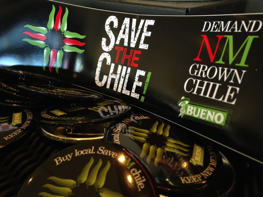 In this July 31, 2013 image, a collection of bumper stickers and buttons promoting New Mexico-grown chile sits on the order counter at Hello Deli restaurant in Albuquerque, N.M. A friendly Super Bowl bet between the mayors of Seattle and Denver has created a stir this week in New Mexico, re-energized efforts to promote the state's famous hot peppers. (AP Photo/Susan Montoya Bryan)