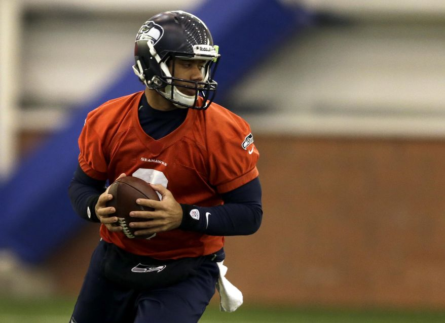 Seattle Seahawks quarterback Russell Wilson drops back during NFL football practice Thursday, Jan. 30, 2014, in East Rutherford, N.J. The Seahawks and the Denver Broncos are scheduled to play in the Super Bowl XLVIII football game Sunday, Feb. 2, 2014. (AP Photo)