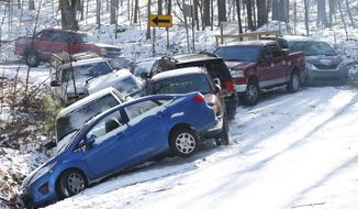 Cars are left abandoned at the bottom of a hill on Grants Mill Road Thursday, Jan.  30,  2014 in Birmingham,  Ala.  The south woke up to more freezing temperatures but officials are hoping for a thaw and relief from the icy conditions. (AP Photo/Hal Yeager)