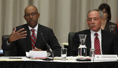 Dr. Michael Drake, left, the incoming president at Ohio State University, speaks during the university board meeting after being voted in as president as Robert Schottenstein, board chairman, looks on Wednesday, Jan. 30, 2014.  (AP Photo/Paul Vernon)