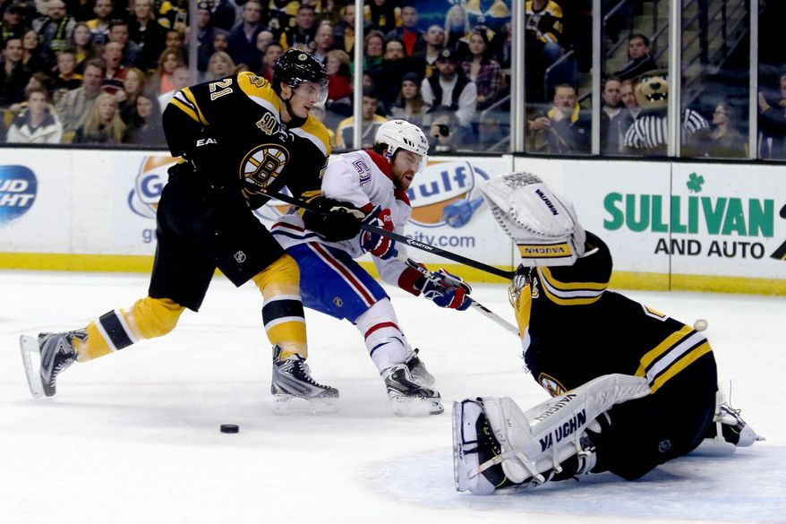 Boston Bruins goalie Tuukka Rask, right, of Finland, makes the save as teammate  Loui Eriksson (21), of Sweden, pushes Montreal Canadiens center David Desharnais (51) away from the puck during the first period of an NHL hockey game on Thursday, Jan. 30, 2014, in Boston. (AP Photo/Mary Schwalm)