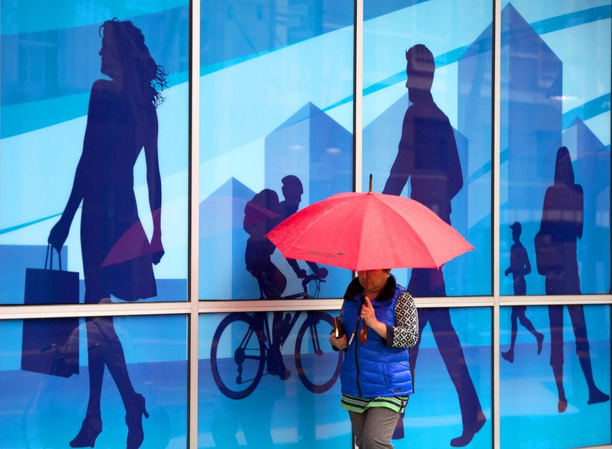 A woman uses an umbrella to shield herself from the rain as she passes by a mural  in the window of an office building on the K Street Mall on Wednesday, January 29, 2013 in Sacramento, Calif. Sacramento had its first rain after 52 days without rain. The National Oceanic and Atmospheric Administration's Web site is predicting a tenth of an inch of rain in San Francisco over the next two days and more than 2 inches in parts of Sacramento. (AP Photo/The Sacramento Bee, Randy Pench)  MAGS OUT; LOCAL TV OUT (KCRA3, KXTV10, KOVR13, KUVS19, KMAZ31, KTXL40); MANDATORY CREDIT