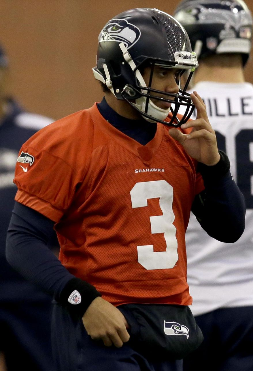 Seattle Seahawks quarterback Russell Wilson adjusts his helmet at the start of NFL football practice Thursday, Jan. 30, 2014, in East Rutherford, N.J. The Seahawks and the Denver Broncos are scheduled to play in the Super Bowl XLVIII football game Sunday, Feb. 2, 2014. (AP Photo)